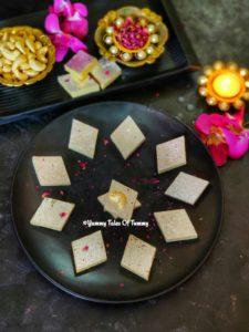 Kaju katli served on a black plate with diyas lit around