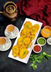 Aloo Pakora served on white tray with green chutney, tomato sauce and tea